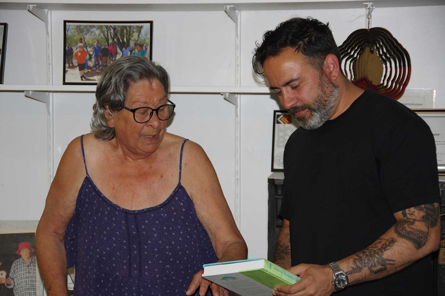 DEG's Virginia Robinson presents Reko Rennie with Gamilaraay / Yuwaalaraay dictionary
